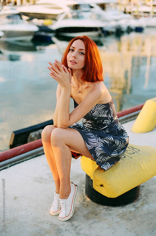 Redhead woman sitting at sea port by Liubov Burakova for Stocksy United