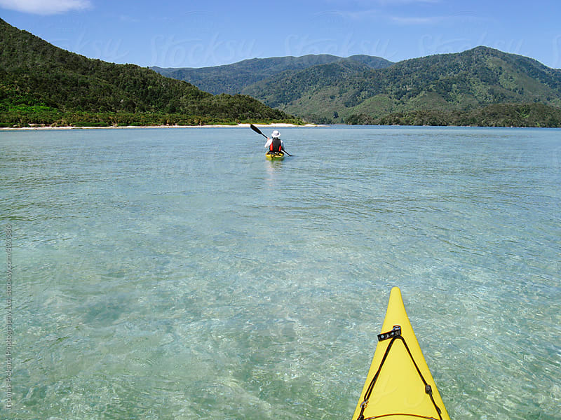 Man paddling a sea kayak, Abel Tasman National Park, New Zealand. by Thomas Pickard for Stocksy United