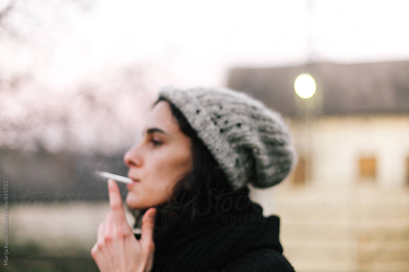 Blurry portrait of a woman smoking cigarette, wearing cap by Marija Kovac for Stocksy United