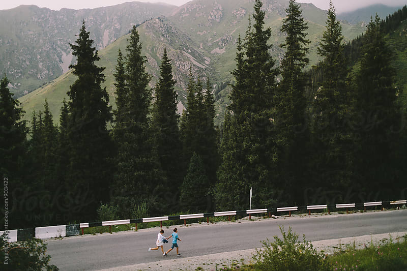 Young couple running on the mountain road by Evgenij Yulkin for Stocksy United