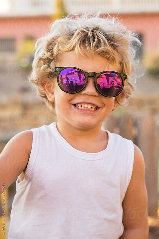 Little blond boy with purple sunglasses looking at camera by ACALU Studio for Stocksy United