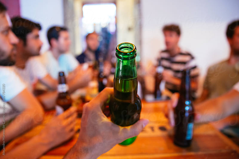 Man hand holding up a full beer bottle in front of camera surrounded by a group of people sitting at a table drinking by Alejandro Moreno de Carlos for Stocksy United