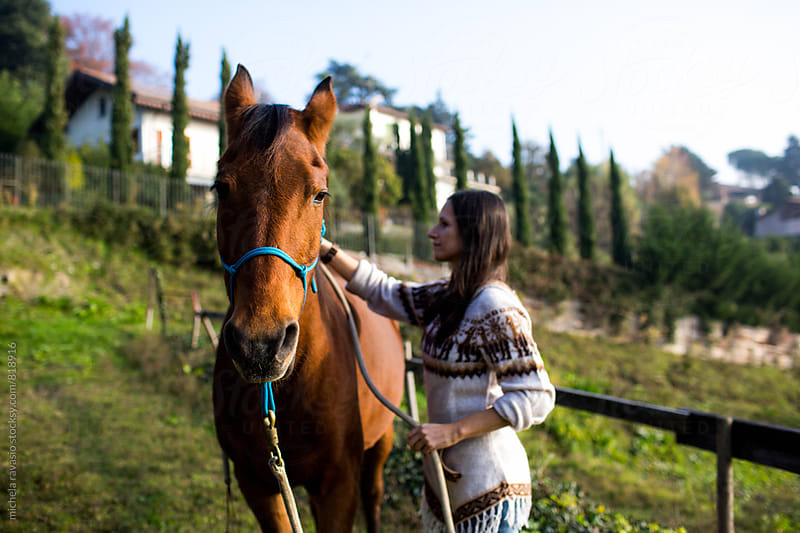 Young woman takes care of her horse by michela ravasio for Stocksy United
