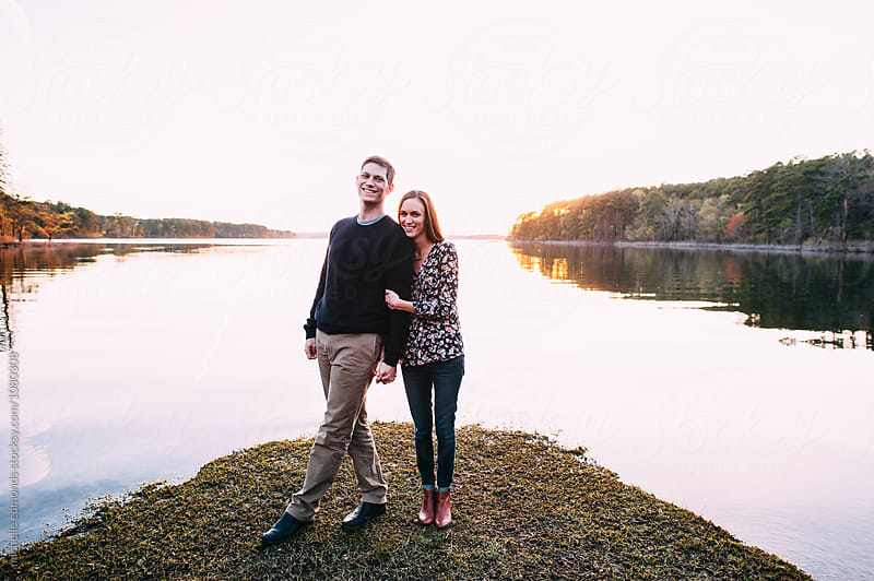 Happy Couple Together on a Pointe in the Lake during Sunset by michelle edmonds for Stocksy United