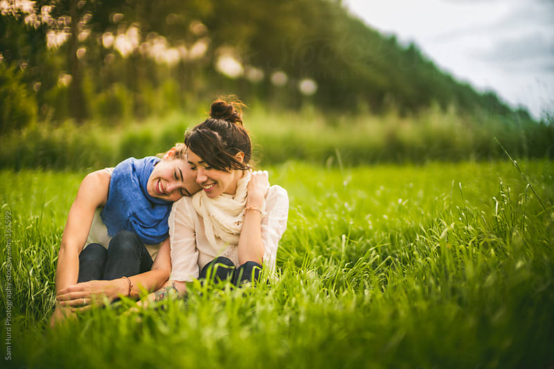 two woman sitting in grass by Sam Hurd Photography for Stocksy United