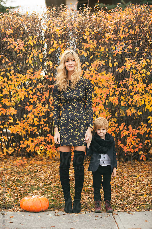 A mother and her son standing on a sidewalk holding hands on a fall day smiling by Ania Boniecka for Stocksy United