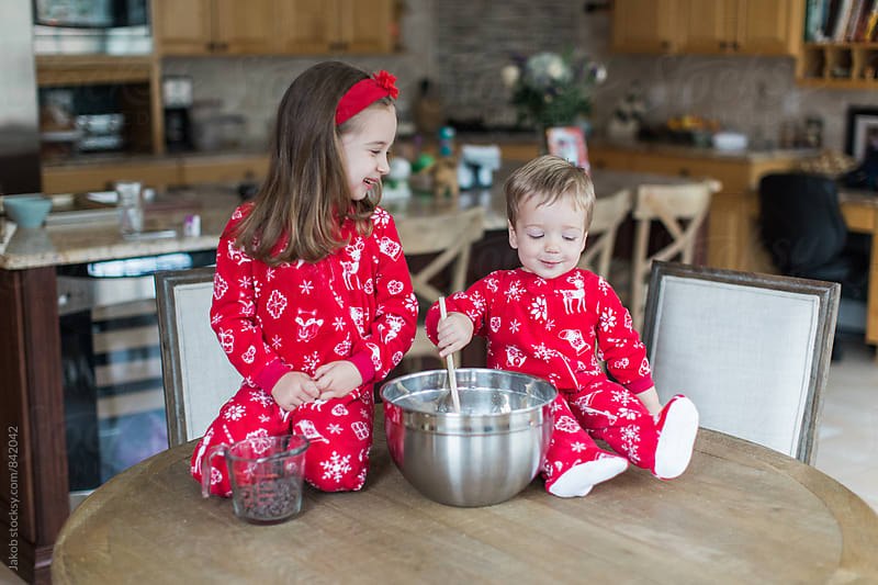 Young boy and girl in christmas onesies making chocolate chip cookies by Jakob for Stocksy United