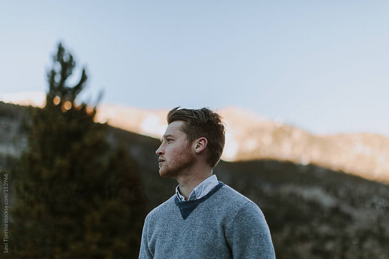 man standing in the shadow of a mountain by Levi Tijerina for Stocksy United
