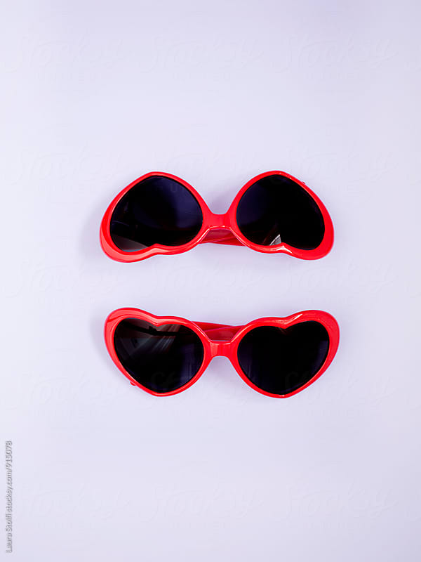 Two heart shaped red sunglasses on lilac background by Laura Stolfi for Stocksy United