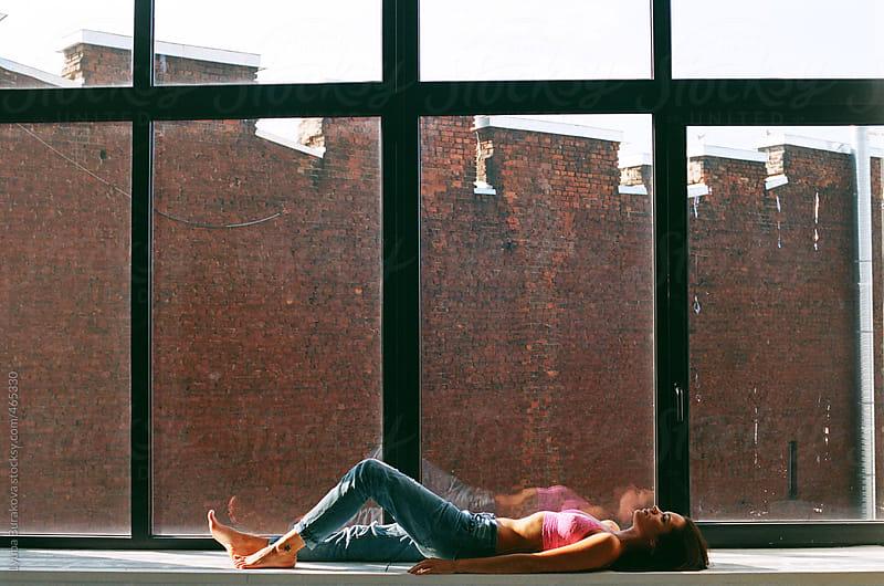 Girl lying on the window-sill by Lyuba Burakova for Stocksy United