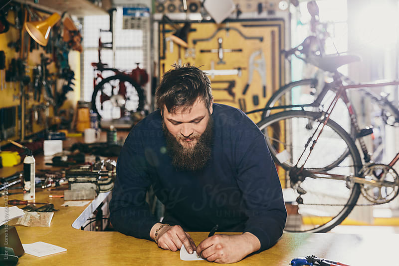 Young mechanic writing on a paper in a workshop by Lior + Lone for Stocksy United