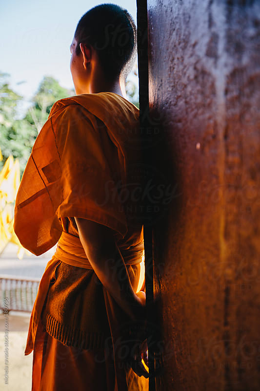 Young Buddhist monk leaning against the door of the temple, back view by michela ravasio for Stocksy United