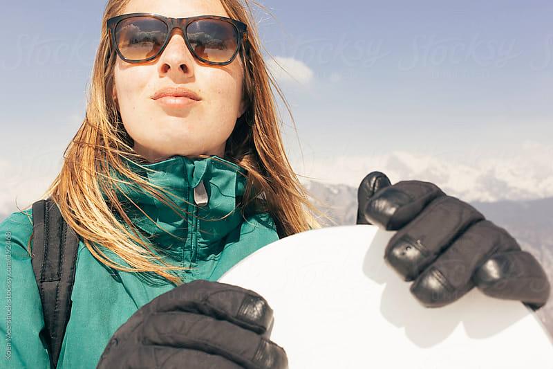 Woman with sunglasses holding her snowboard. by Koen Meershoek for Stocksy United