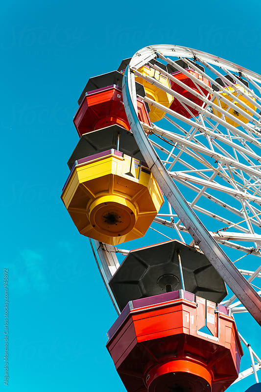 Bright ferris wheel against of blue sky by Alejandro Moreno de Carlos for Stocksy United