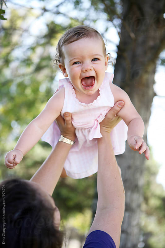 Mom Holding Very Happy Baby Girl In The Air by Dina Giangregorio for Stocksy United