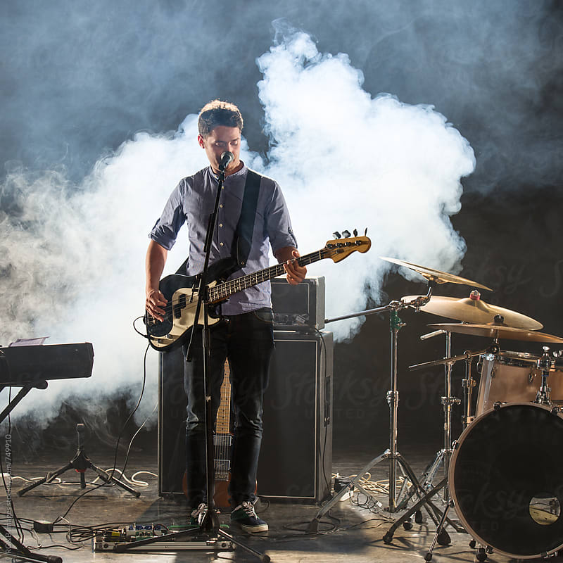 Male musician playing an electric bass guitar on stage by RG&B Images for Stocksy United