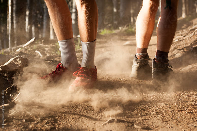 Hiking Feet in Dust. by K. Howard for Stocksy United