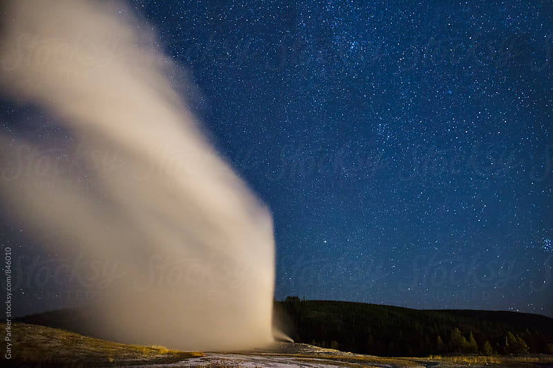 Old Faithful Geyser under the stars at Yellowstone National Park by Gary Parker for Stocksy United