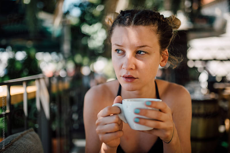 Young woman enjoying coffee outdoor by Boris Jovanovic for Stocksy United