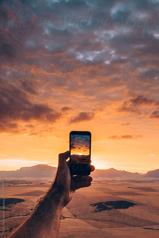 Point of view of a person taking a photo of a sunset with a mobile phone by Micky Wiswedel for Stocksy United