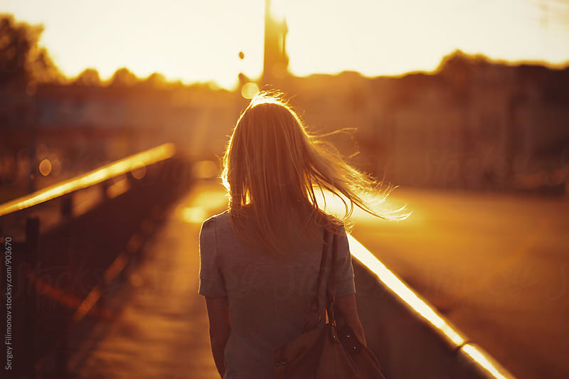 Anonymous young blonde woman walks at sunset by Sergey Filimonov for Stocksy United