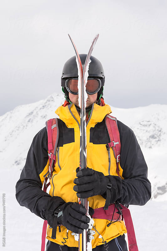 Skier hiding behind his skis by RG&B Images for Stocksy United