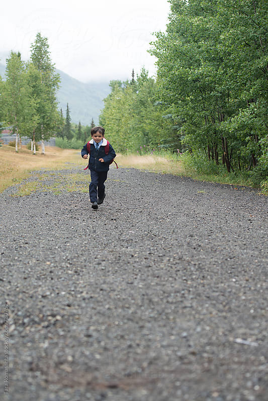boy runs down a path on his way to school by Tara Romasanta for Stocksy United