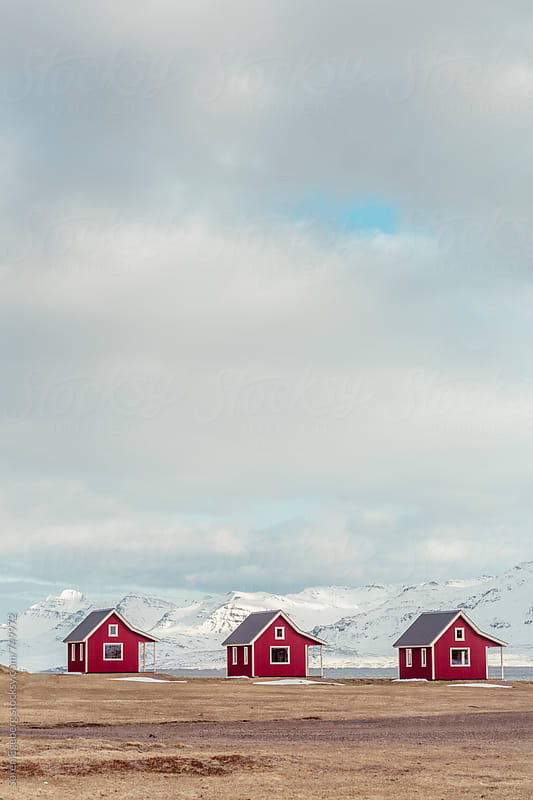 Traditional red Icelandic houses by the mountains in winter by Søren Egeberg Photography for Stocksy United