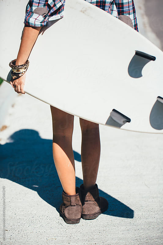 Woman walking with her surfboard by michela ravasio for Stocksy United