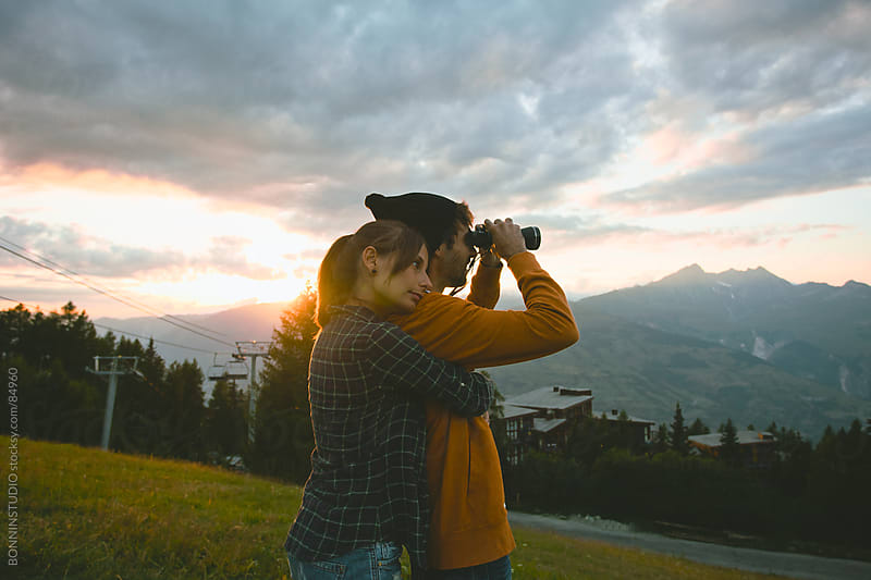 Woman embraced with man looking with binoculars. Beautiful landscape. by BONNINSTUDIO for Stocksy United