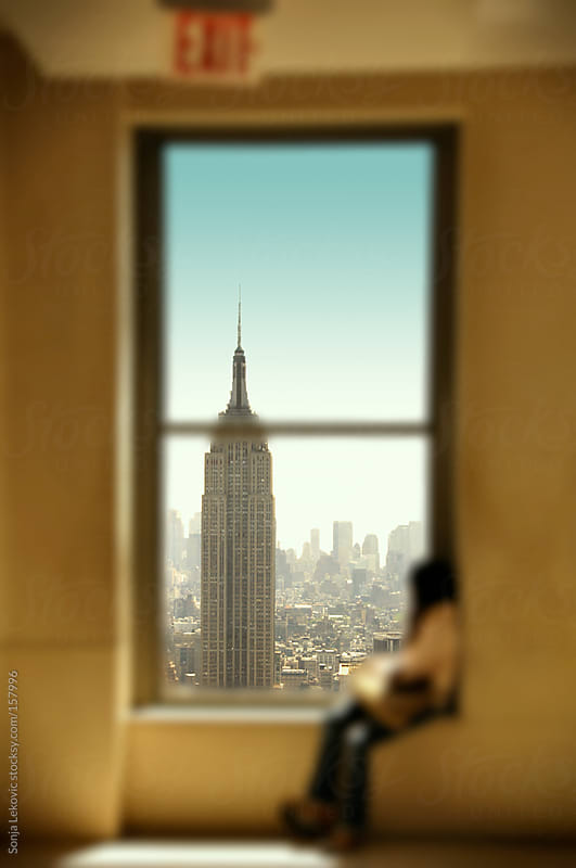 woman looking through a window at new york  by Sonja Lekovic for Stocksy United