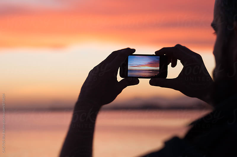 taking a photo of the sunset by Blai Baules for Stocksy United