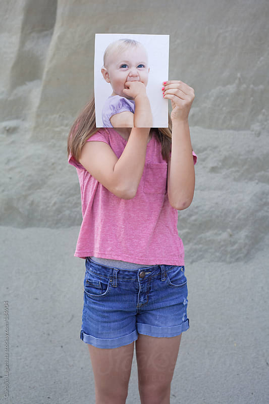 Teen (tween) girl holding her baby picture in front of her face by Carolyn Lagattuta for Stocksy United