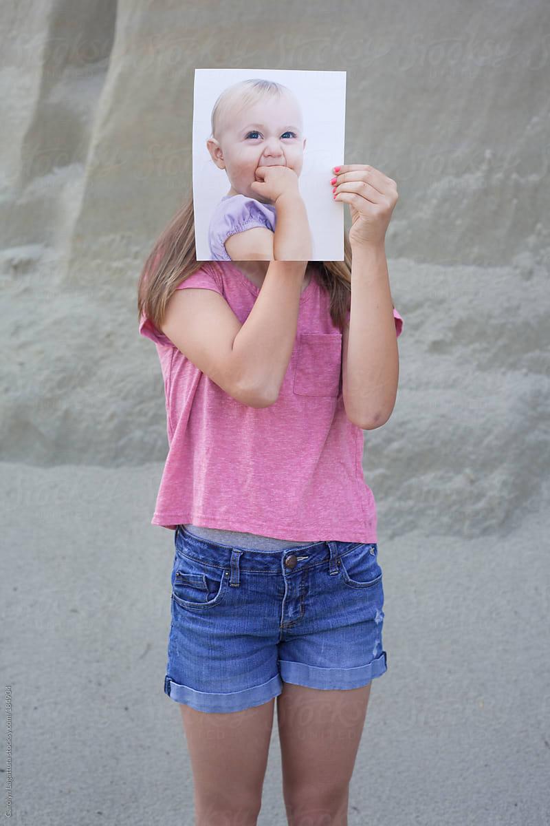 Teen (tween) Girl Holding Her Baby Picture In Front Of Her