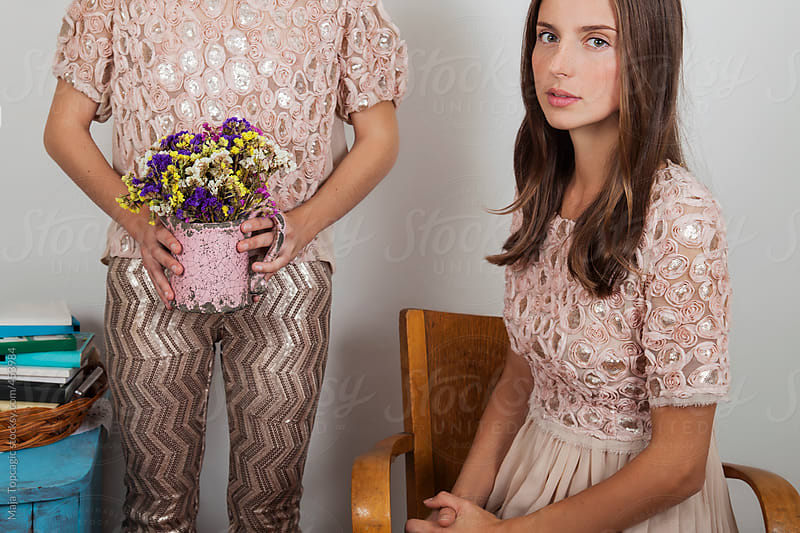 Young beautiful woman in a pink dress holding flowers by Maja Topcagic for Stocksy United