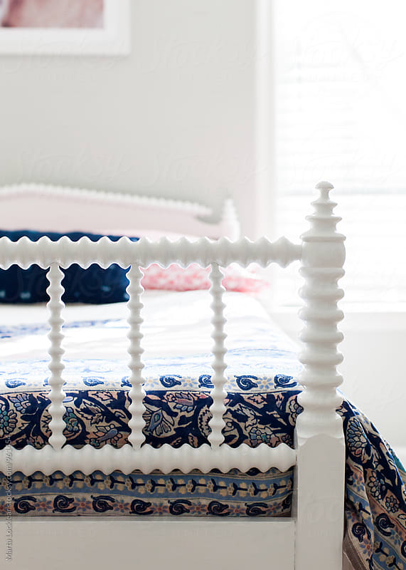 Antique white bed in girls room by Marta Locklear for Stocksy United