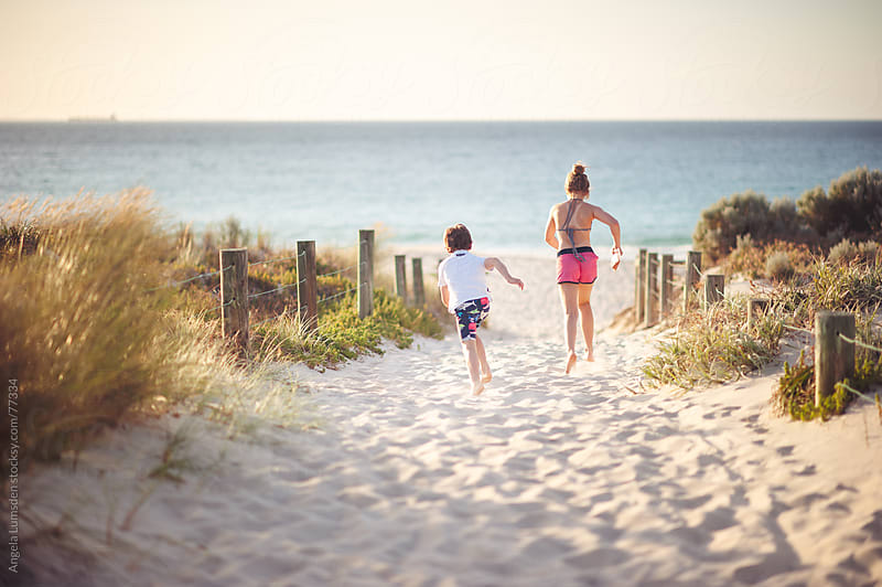 Children running through sand dunes towards the ocean by Angela Lumsden for Stocksy United