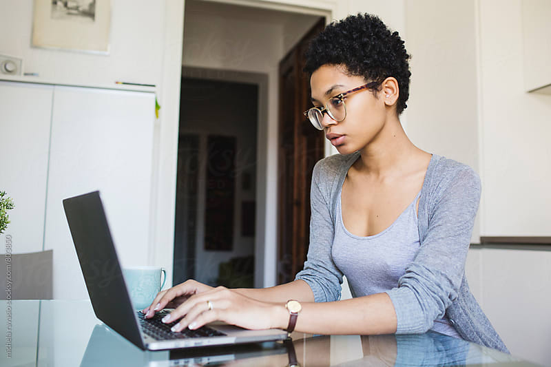 Young woman using her laptop in the kitchen by michela ravasio for Stocksy United
