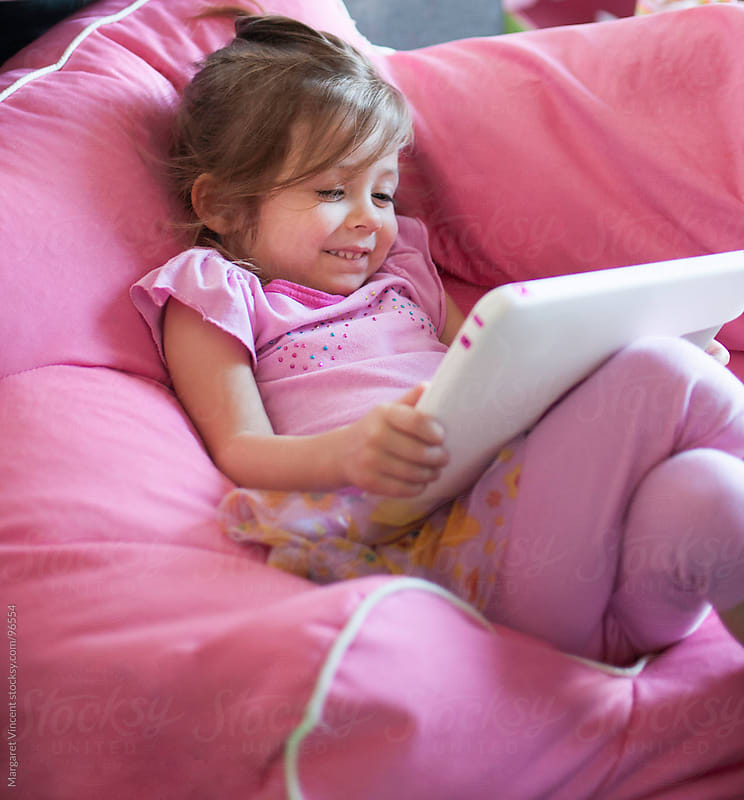 little girl plays on tablet by Margaret Vincent for Stocksy United