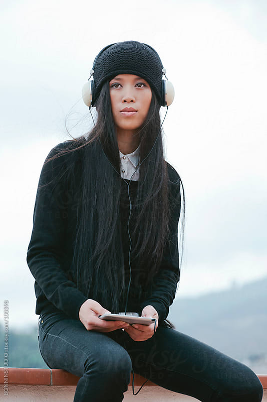 Young chinese woman listening music on tablet sitting on the roof. Winter scene. by BONNINSTUDIO for Stocksy United
