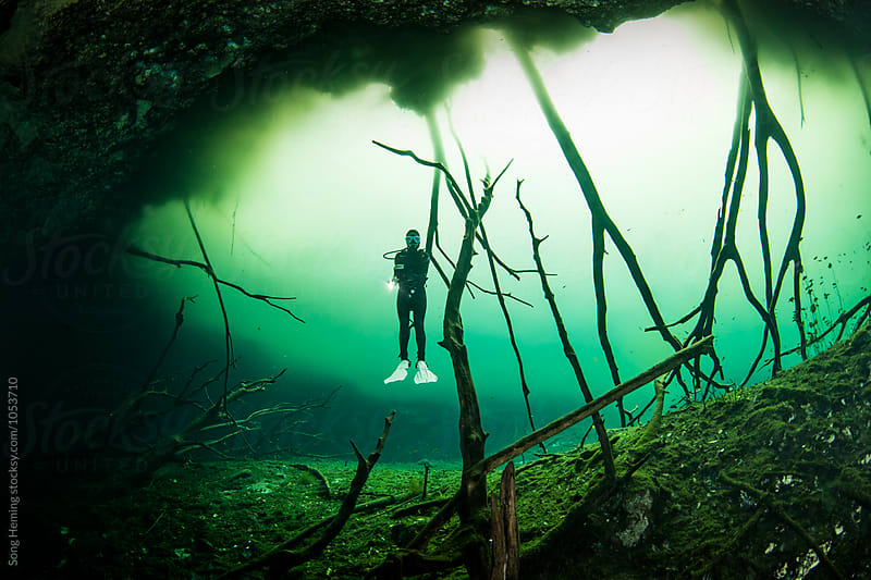 A scuba diver swimming in Mexico's  Cenote Car Wash by Song Heming for Stocksy United