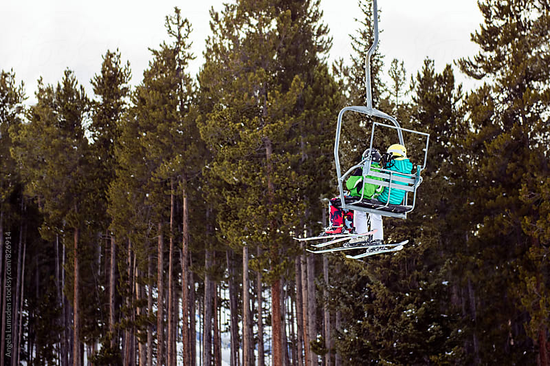 Two children with skis and ski clothes riding a chair lift together by Angela Lumsden for Stocksy United