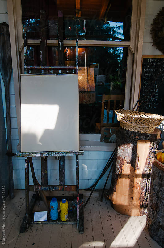 blank easel on a sun-lit porch by Margaret Vincent for Stocksy United