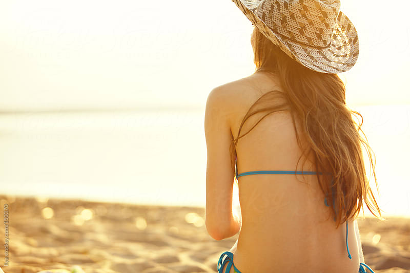 Rear view of young slim woman wearing a hat and bikini on the beach by Ilya for Stocksy United