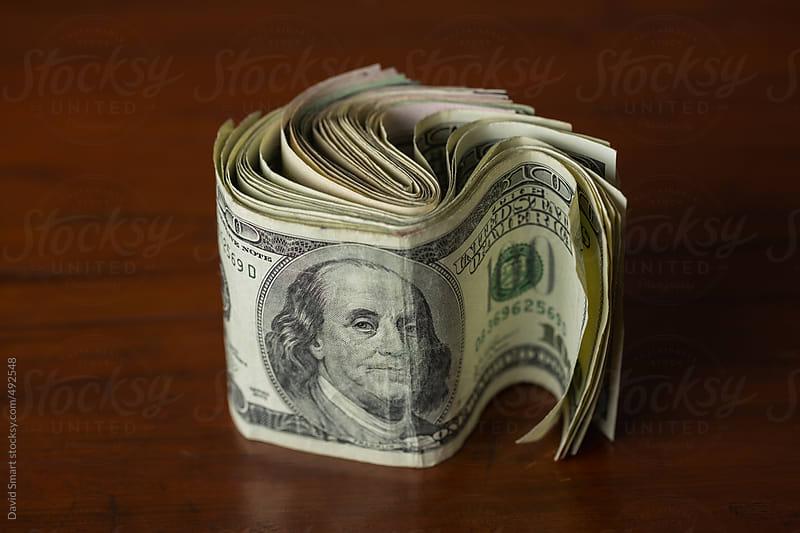Several US one hundred dollar bills on dark tabletop by David Smart for Stocksy United