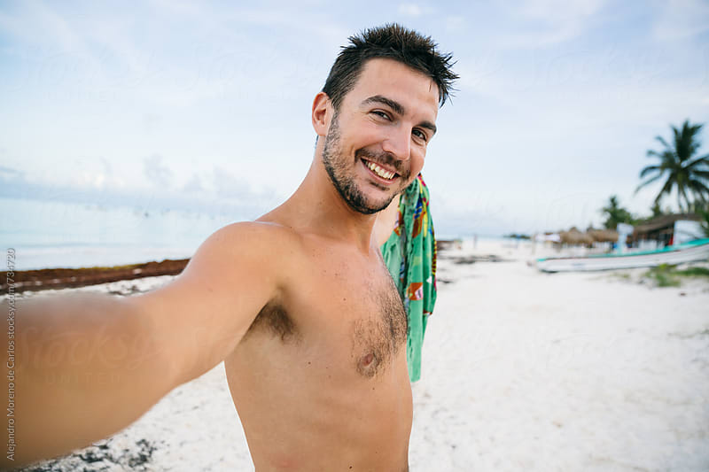 Young man taking a selfie in a tropical beach at sunset by Alejandro Moreno de Carlos for Stocksy United