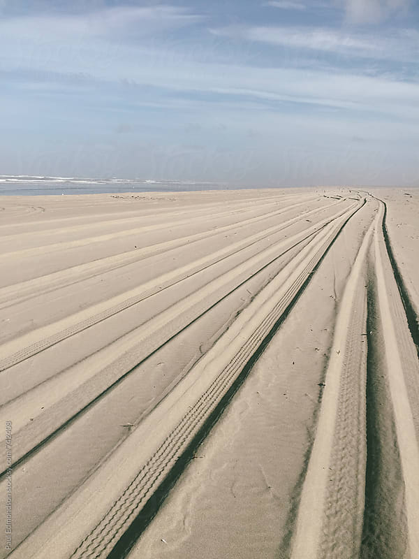 Tire tracks on beach by Paul Edmondson for Stocksy United