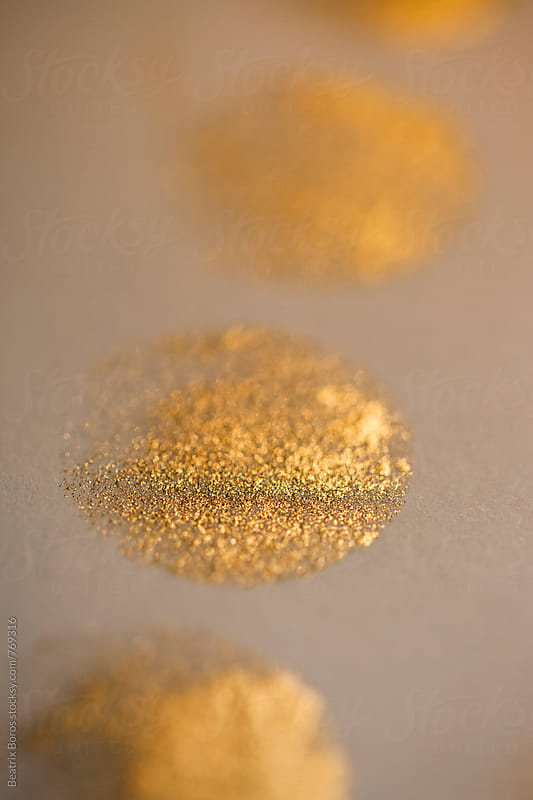 Planet shaped circles made of glittery golden paint by Beatrix Boros for Stocksy United