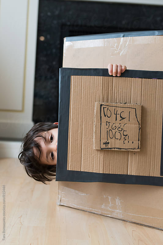 young child peeking out of a cardboard box, sideways by Tara Romasanta for Stocksy United