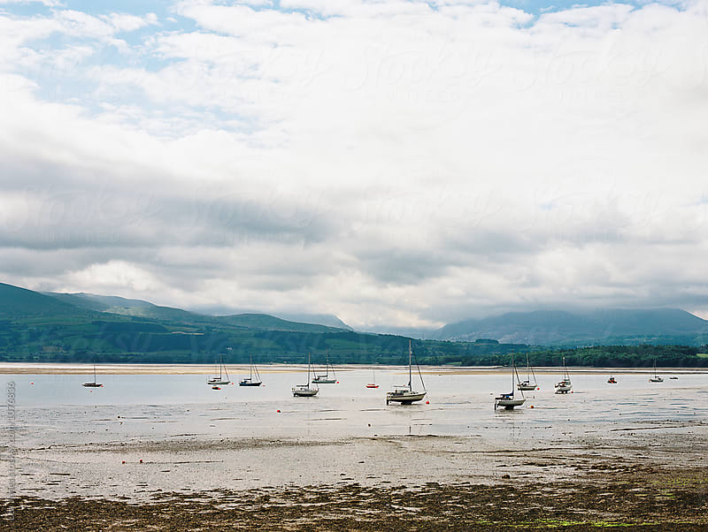 sailing boats at low tide in Wales by Léa Jones for Stocksy United